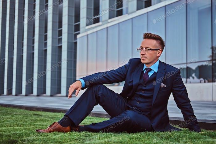 Уверенный бизнесмен, одетый в элегантный костюм, сидящий на зеленой лужайке на фоне городского пейзажа.
