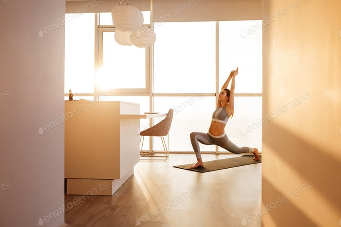 Young lady that practicing yoga poses on yoga mat at home with big beautiful windows on background