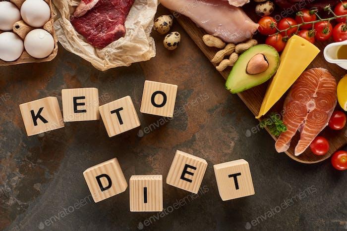 Alimentos ricos en grasa cerca de cubos de madera con inscripción de dieta cetogénica