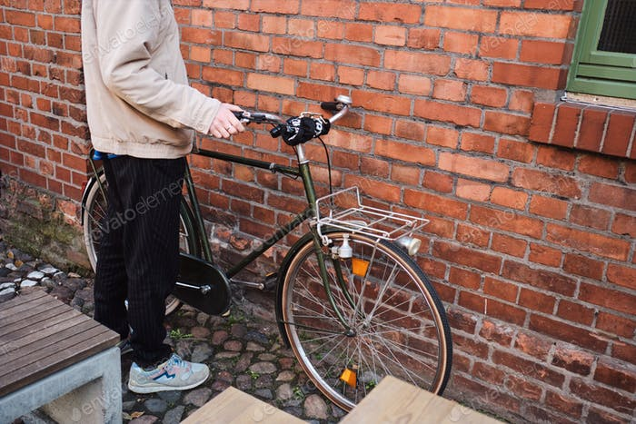 Close up man parking his bicycle near brick wall outdoor