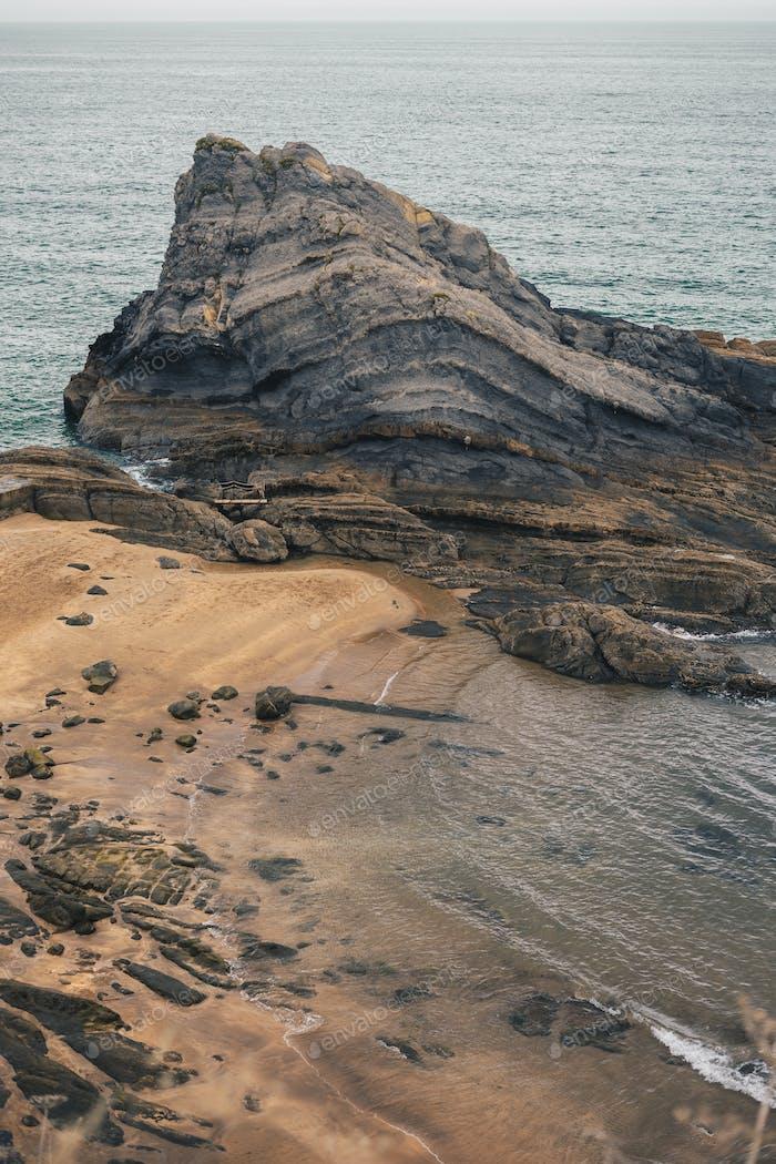 Wild beach with rocks and sea entrances