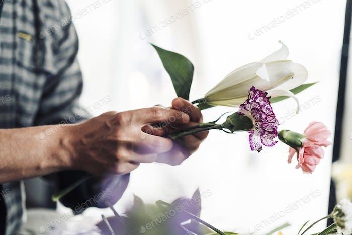 Joven florista masculino trabajando en floristería