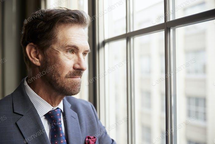 Senior weißer Geschäftsmann schauend aus dem Fenster, Nahaufnahme