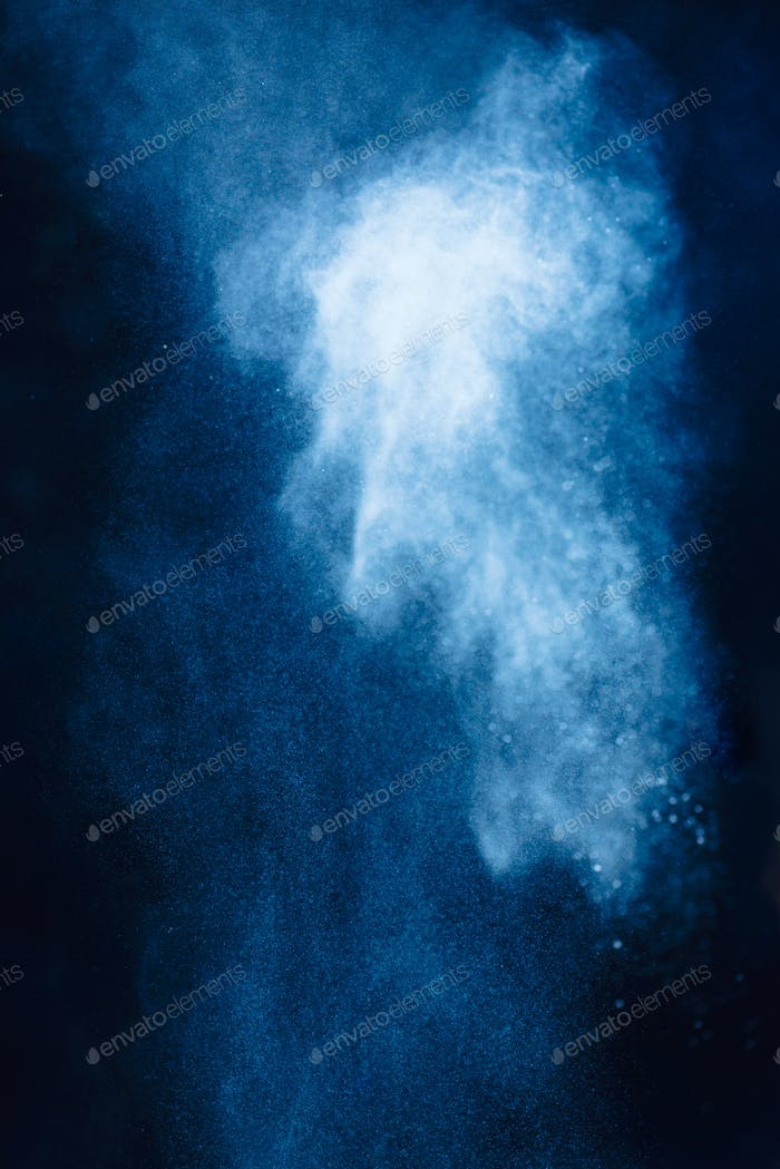 Flour powder explosion in motion. Action food photography. Light blue dust on a black background