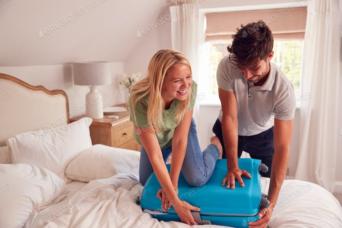 Couple In Bedroom Struggling To Close Over Packed Suitcase For Vacation