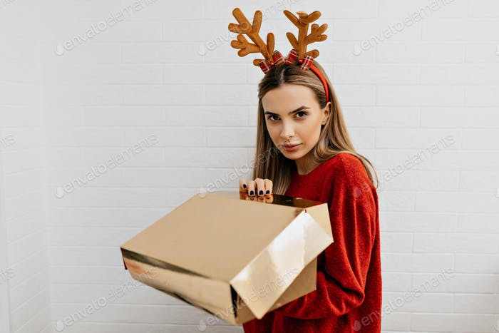 Studio shot of styling woman is opening gold present in christmas headgear looking at camera