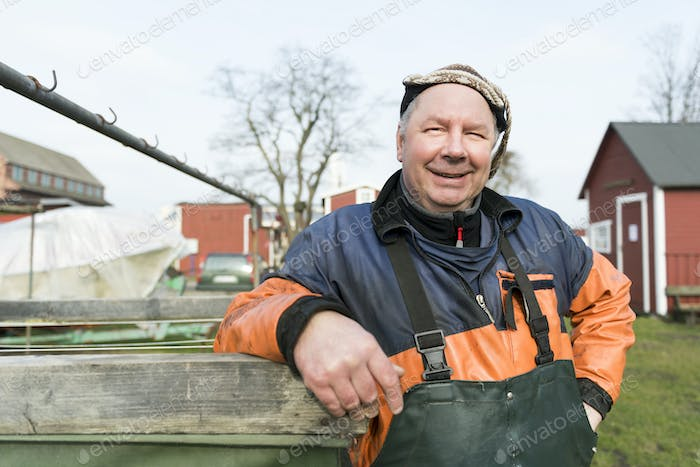 Portrait of happy mature fisherman in protective workwear outside fishing industry