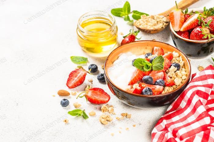 Griechischer Joghurt Müsli mit frischen Beeren auf weißem Stein Tisch