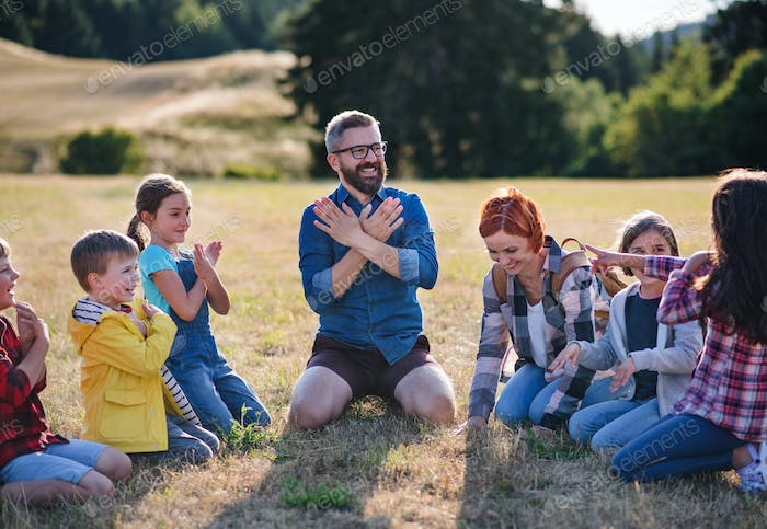 Group of school children with teacher on field trip in nature, chanting.