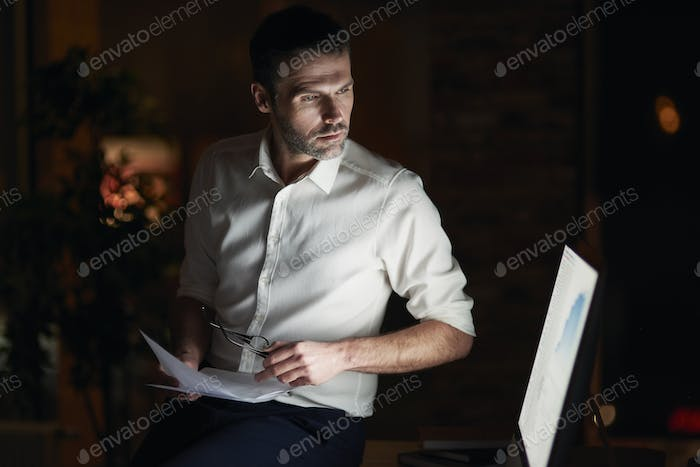 Serious man analyzing document in his office