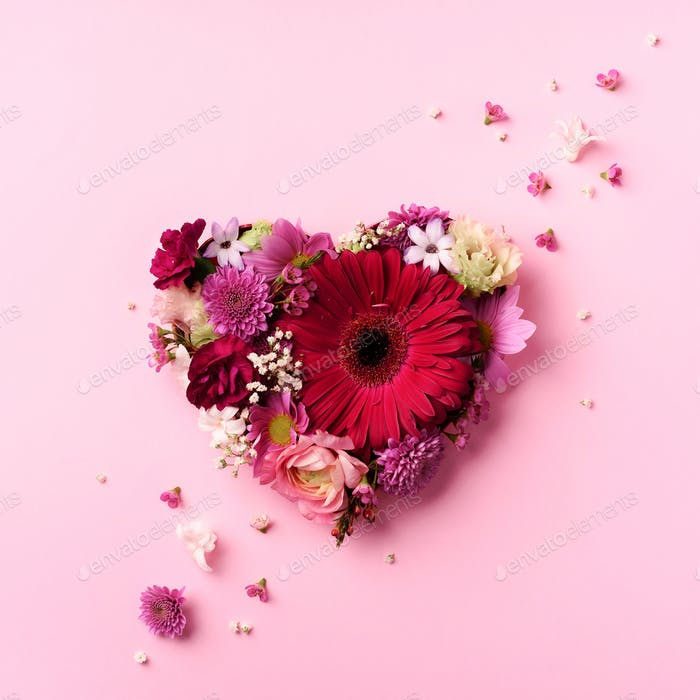 Heart shape made of spring flowers on pink punchy pastel background. Top view, flat lay. Summer