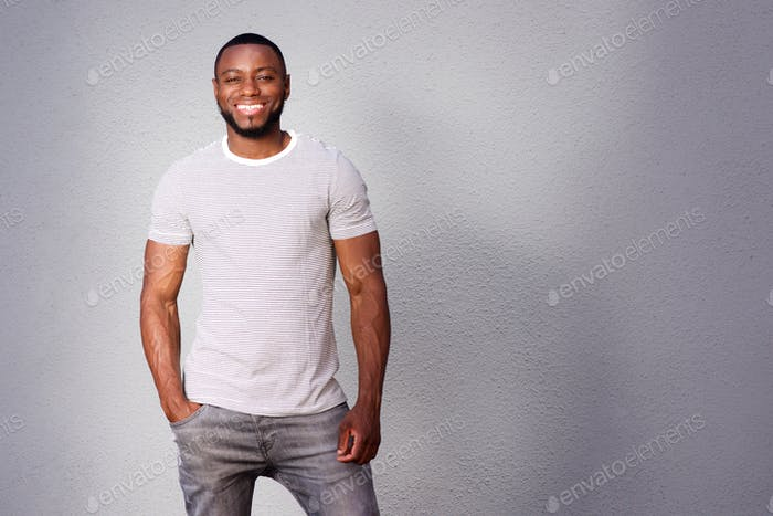 muscular man smiling and standing against gray background