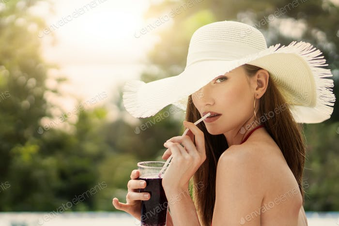 Portrait Of A Beautiful Girl In A Hat Who Drinks Juice Near The Pool