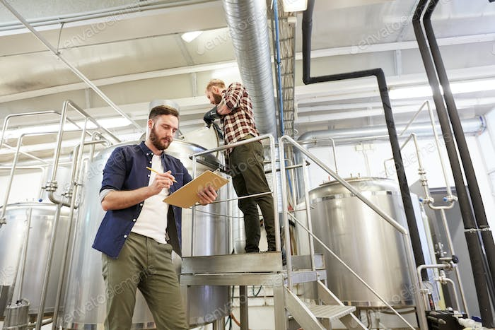 men with clipboard at brewery or beer plant