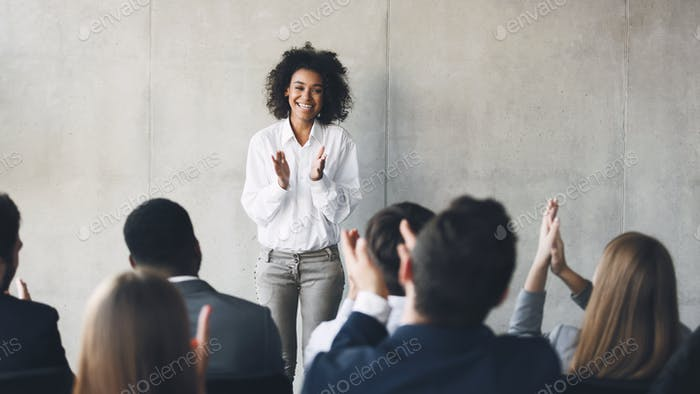 Business presentation. Grateful audience clapping hands to speaker