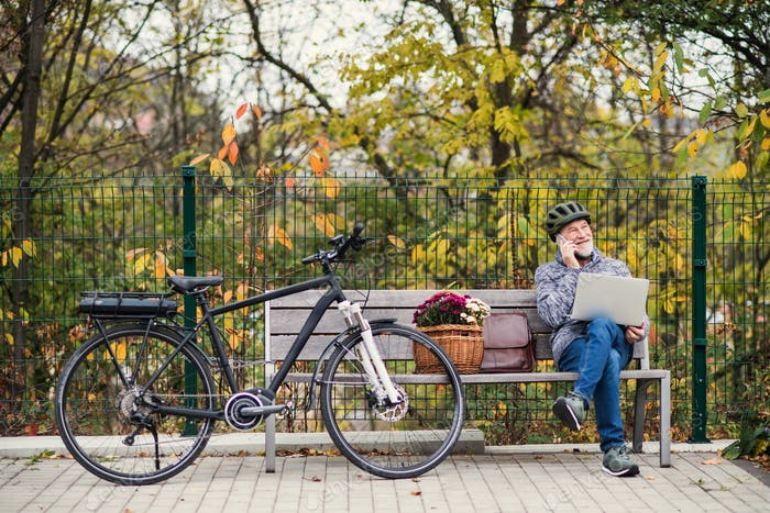 Senior man with electrobike sitting on a bench outdoors in town, using laptop and smartphone.