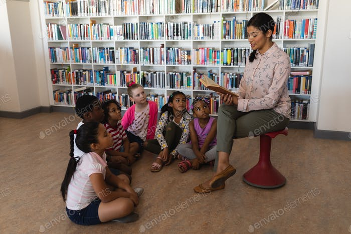 Female teacher reading a story to schoolkids in school library