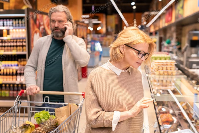 Blond mature woman in eyeglasses looking at grilled poultry on display
