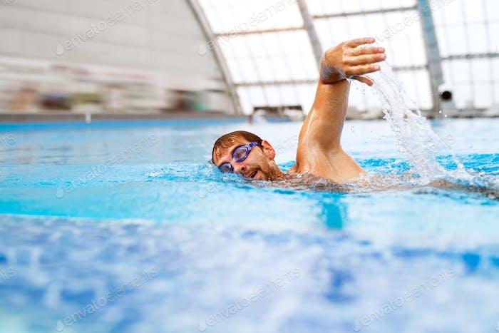 Mann schwimmen in einem Hallenbad.