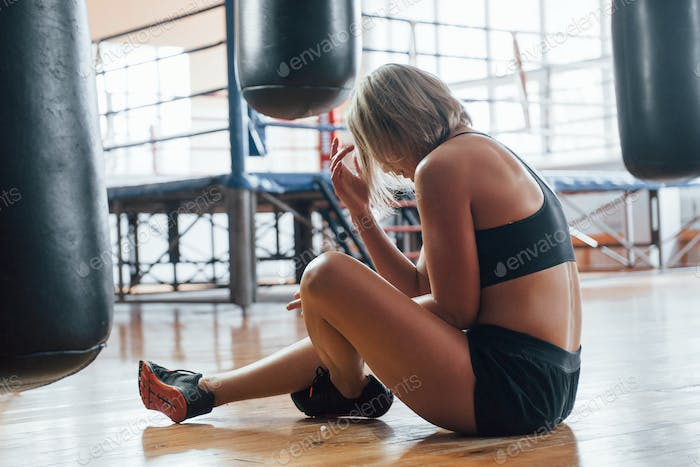 Sits on the floor after training. Tired after workout. Having rest in the gym for box sport training