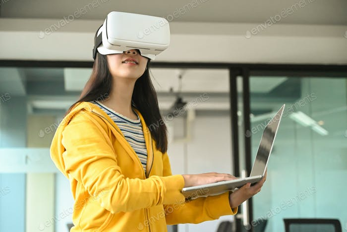 Asian girl wearing a yellow shirt, using VR headset. She is holding laptop and typing a keyboard.