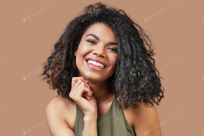Beautiful young African woman in casual clothing smiling and looking at camera