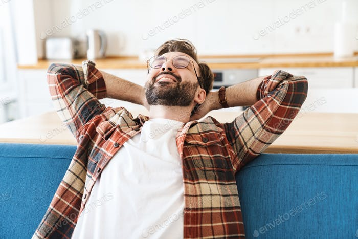 Portrait of happy bearded man smiling while sitting on sofa at home