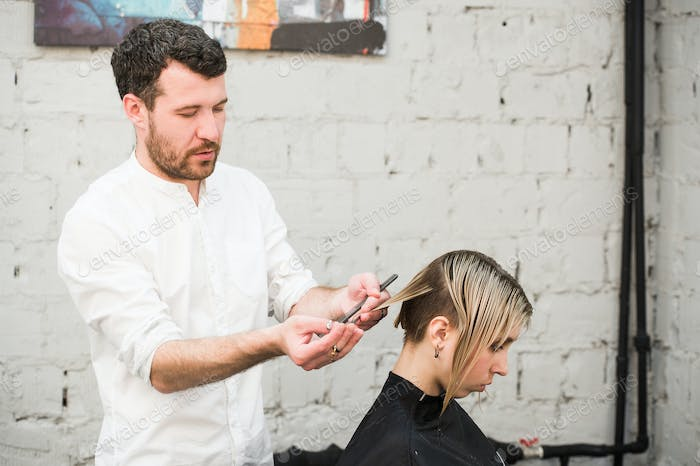 hairdresser cuts hair with scissors on crown of handsome satisfied client in professional