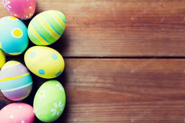 close up of colored easter eggs on wooden surface