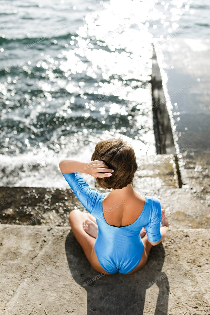 Beautiful woman sitting with her back and meditating by the sea