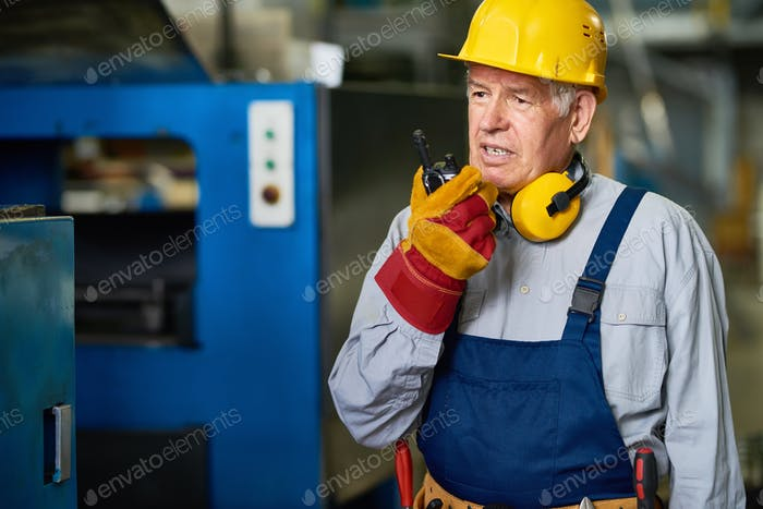 Factory Foreman Speaking by Radio Set