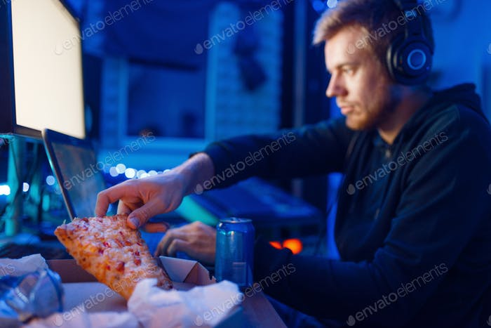 Male gamer eating pizza, night tournament