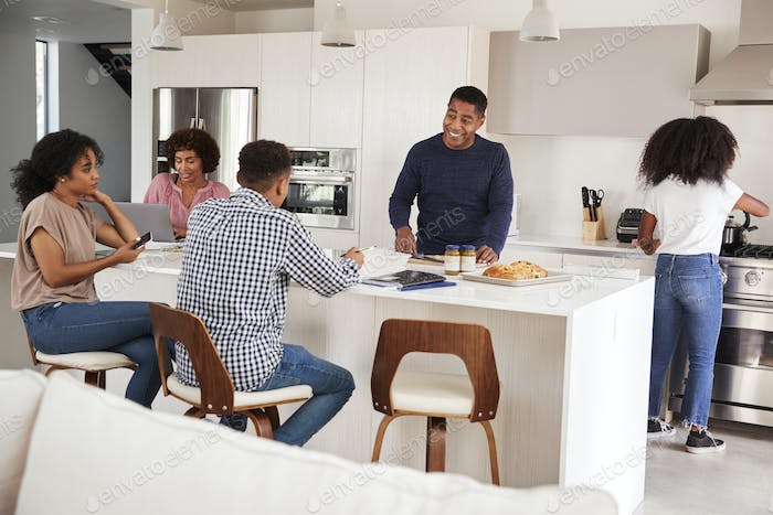 Happy black family talking and preparing a family meal together in their kitchen