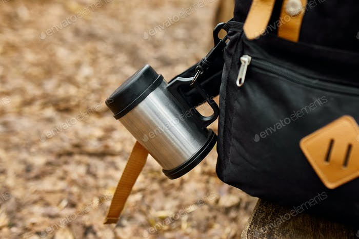 Travel backpack with accessory on autumn background, local travel,