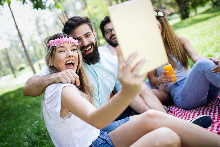 Happy young friends having fun outside in nature, taking selfie