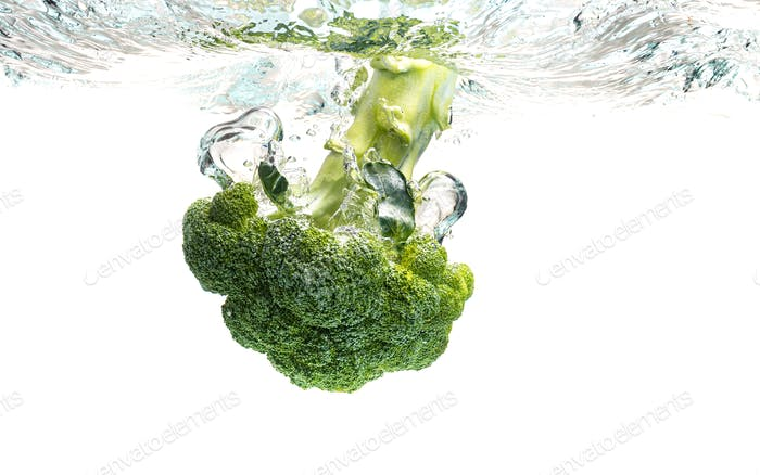 Green broccoli falling in water with splash on white with air bubbles