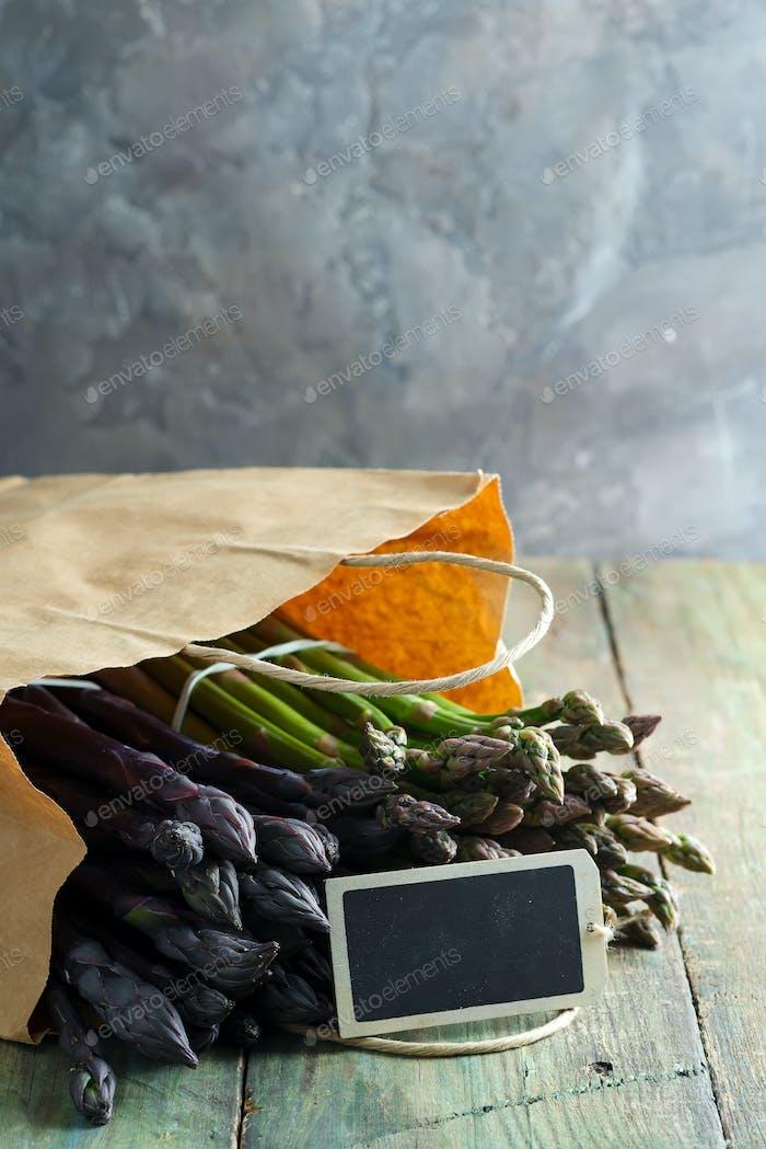 Papiertüte mit frisch gepflückten rohen organischen natürlichen lila Spargelspeeren auf Holzhintergrund