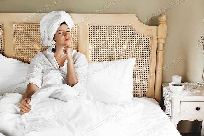 Стильная счастливая молодая женщина отдыхает в постели