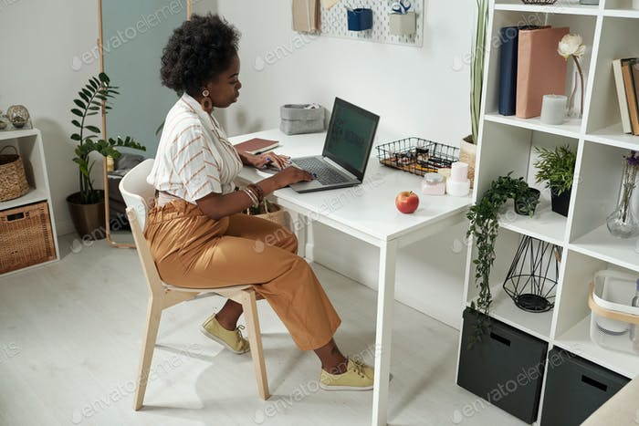 Young contemporary businesswoman networking by desk at home
