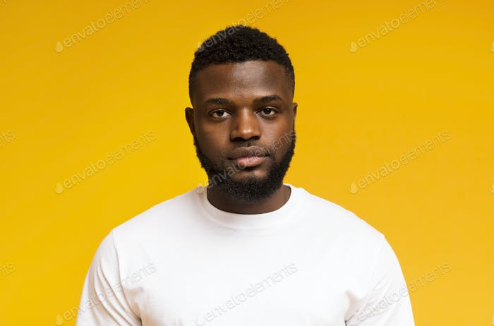 Serious young african american man portrait on yellow background