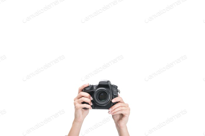 cropped view of female hands taking photo on professional camera, isolated on white