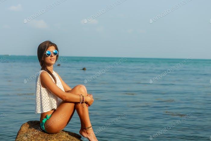 Sinnliches Mädchen auf großen Stein in der Nähe von Wasser.