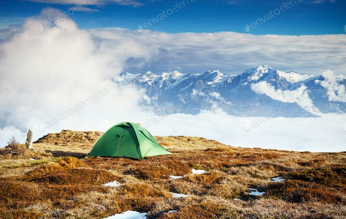 Tent against the backdrop of snow-capped mountain peaks. The view from the mountains to Mount Ushba