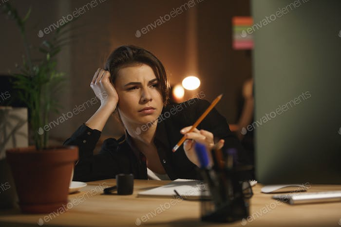 Tired woman with pencil working with computer
