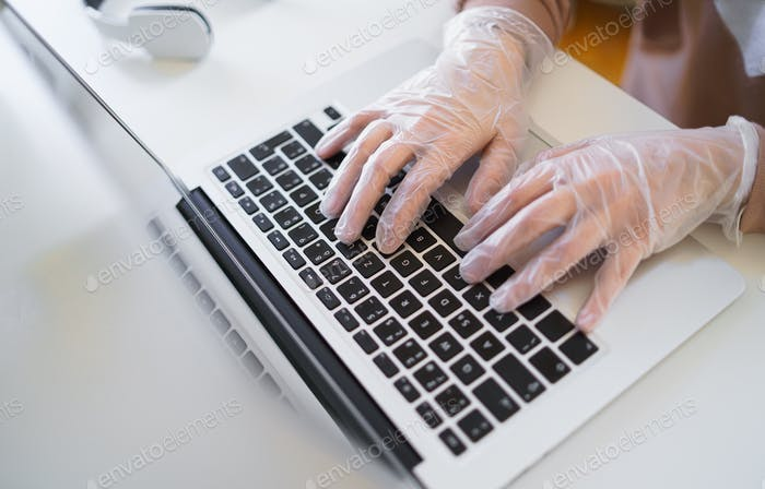 Unrecognizable woman with gloves at the table, using laptop in quarantine