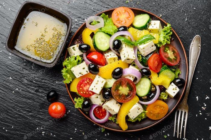 Top view at Mediterranean diet dish greek salad on slate tray wi