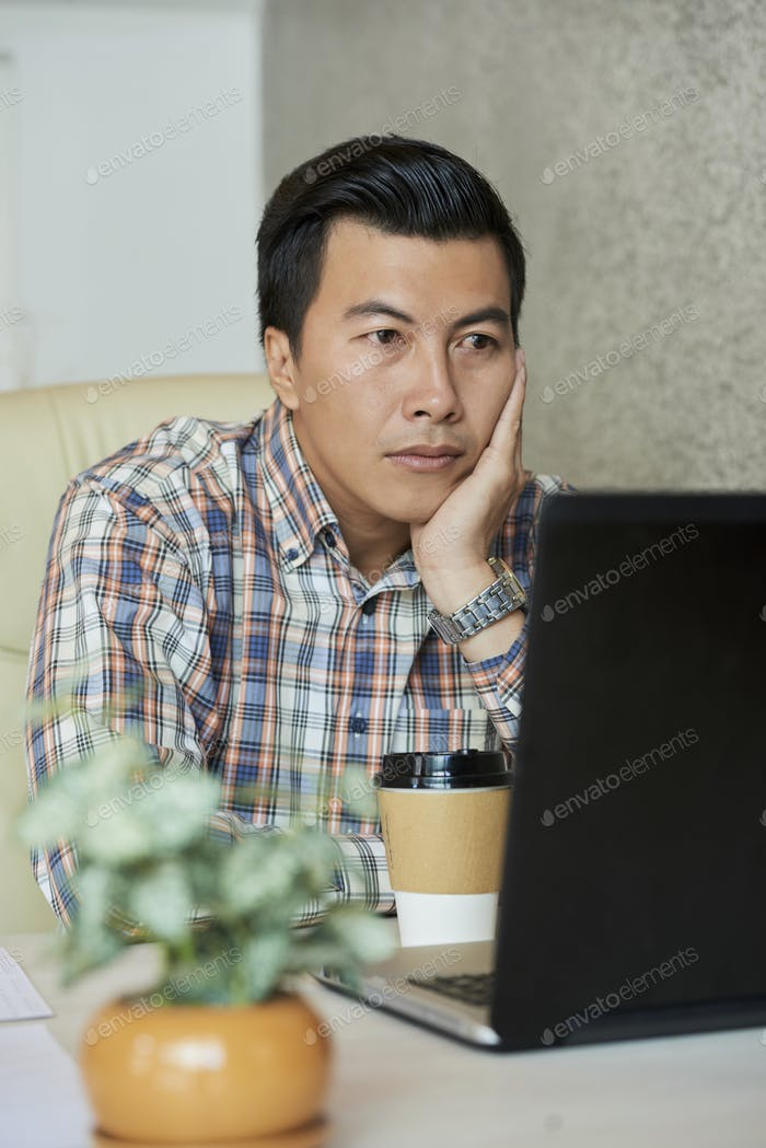 Exhausted businessman looking at laptop screen