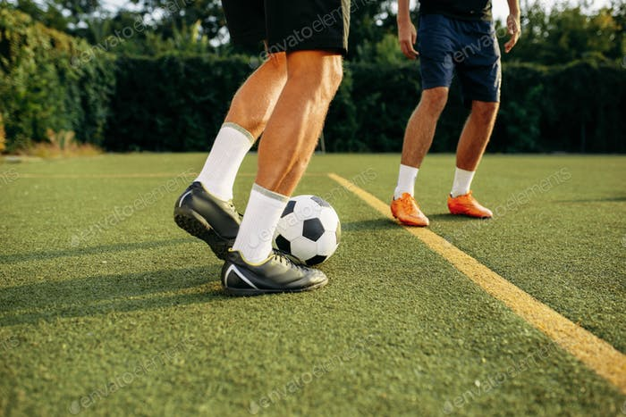 Male soccer players playing with ball on line