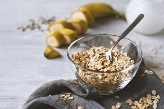 Oat flakes in a glass bowl on the wooden table