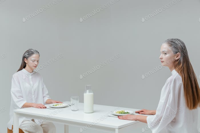 Two women sitting at the table with food
